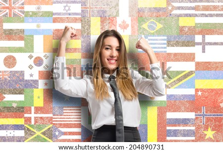 Young businesswoman winning over flags background  - stock photo