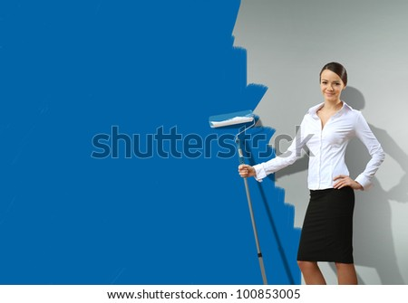 Young businesswoman with a paint brush against blue wall - stock photo