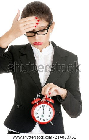 Young businesswoman with a red clock in distress. Isolated on white. - stock photo