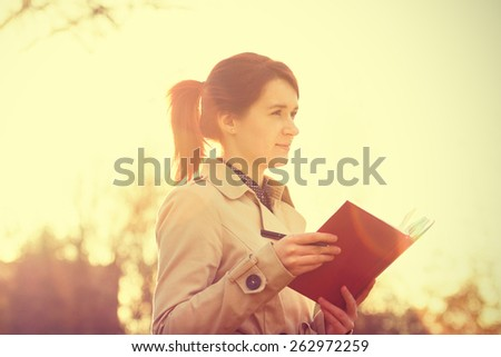 Young businesswoman with a thoughtfully emotion,student professional outdoors holding a red journal.Businesswoman,Life style. - stock photo