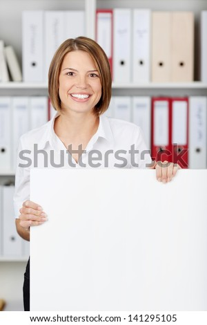Young businesswoman with big white board at office - copyspace for text - stock photo