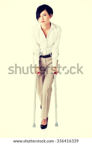 Young businesswoman with crutches. Disabled person in work.