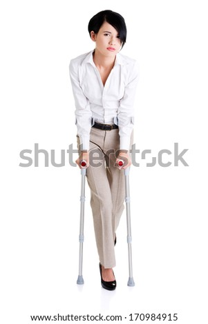 Young businesswoman with crutches, isolated on white. Disabled person in work.