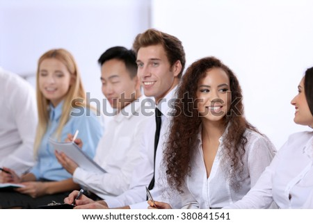Young businesswoman with curly hair talking to colleague at the office meeting