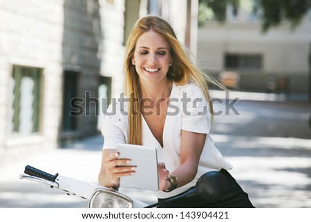 Young businesswoman with digital tablet on a scooter. Blonde woman standing on the street. - stock photo
