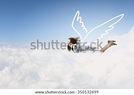Young businesswoman with drawn wings flying high in sky - stock photo