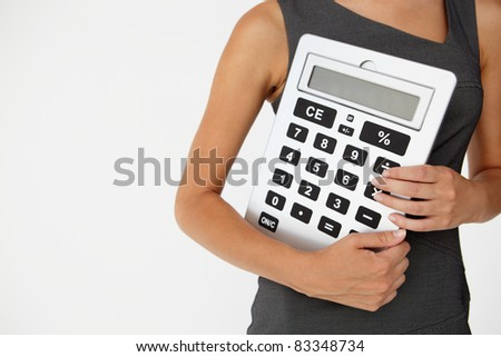 Young businesswoman with giant calculator - stock photo