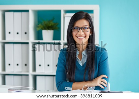 Young businesswoman with glasses working in modern office - stock photo