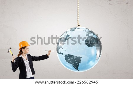 Young businesswoman with hammer hitting nail in Earth planet - stock photo