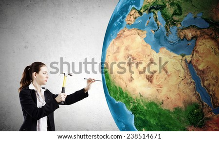 Young businesswoman with hammer hitting nail in Earth planet. Elements of this image are furnished by NASA - stock photo