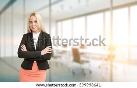Young businesswoman with hands crossed. Blurred office at background. Concept of work.