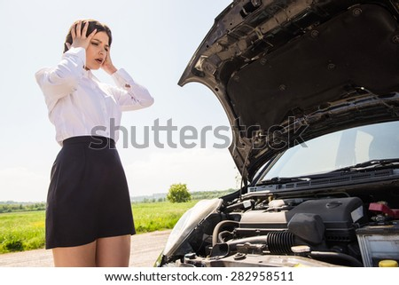 Young businesswoman with hands on head standing by broken down car at countryside. - stock photo