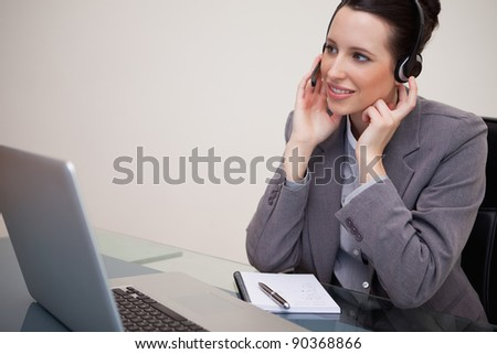Young businesswoman with headset sitting at her desk