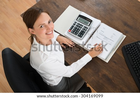 Young Businesswoman With Invoice And Calculator At Wooden Desk - stock photo