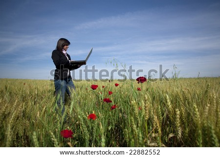 young businesswoman with laptop on poppy field - stock photo