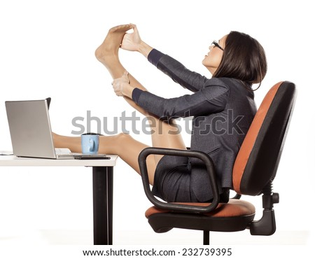 young businesswoman with legs on the table massaged her foot - stock photo