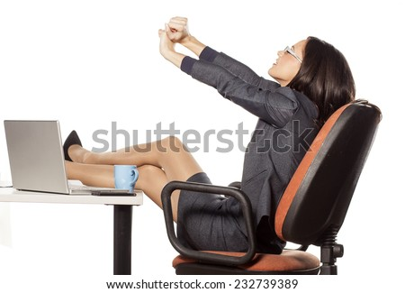 young businesswoman with legs on the table stretches her hands - stock photo