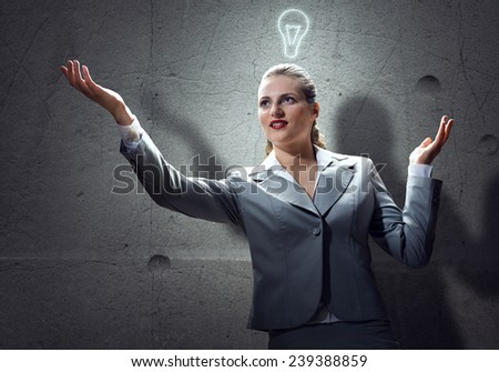 Young businesswoman with light bulb above head - stock photo