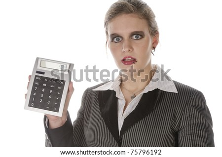 Young businesswoman with lip piercing in a gray business suit and high heels looks anxiously at her pocket calculator, isolated on a white background - stock photo