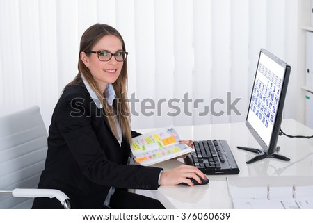 Young Businesswoman With List Of Work In Diary Looking At Computer