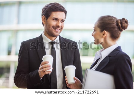 Young businesswoman with male colleague discussing. businessman and businesswomen drinking coffee outside - stock photo