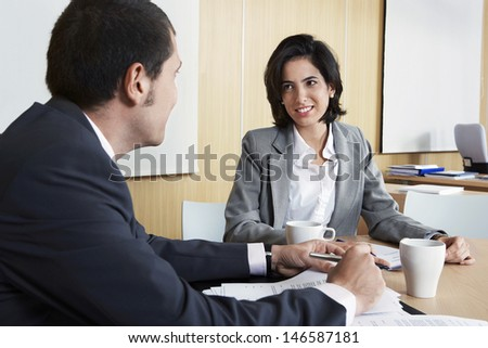 Young businesswoman with male colleague discussing in office - stock photo