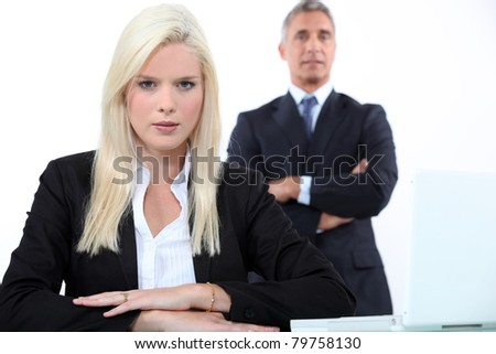 Young businesswoman with older male colleague - stock photo