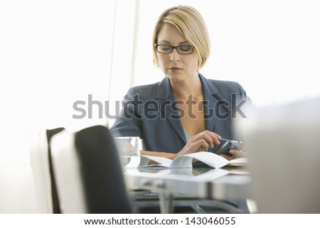 Young businesswoman with paperwork using cell phone in conference room - stock photo