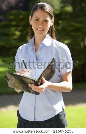 Young businesswoman with pen and folder outdoors, smiling, portrait
