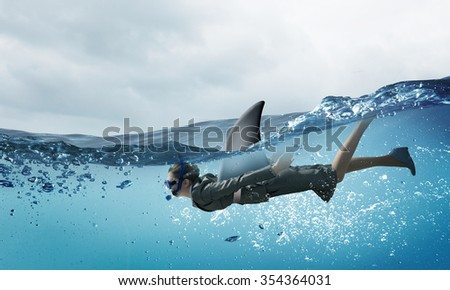 Young businesswoman with shark flipper swiming under water - stock photo