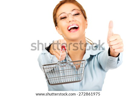 Young businesswoman with shopping cart and thumbs up. - stock photo