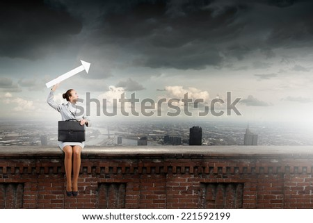 Young businesswoman with suitcase sitting on top of building