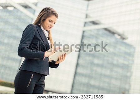 Young businesswoman with tablet in front of office building