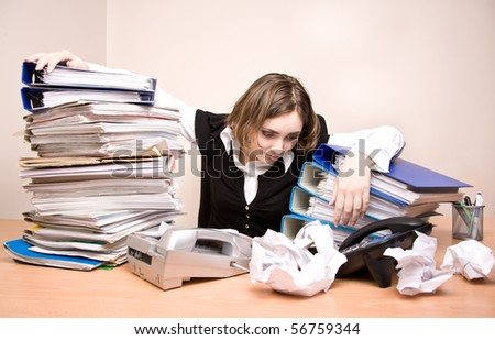 Young businesswoman with tons of documents at office