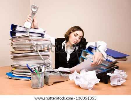 Young businesswoman with tons of documents calling phone - stock photo
