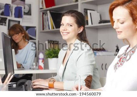 Young businesswoman working in graphic studio with colleagues. Small business.  - stock photo