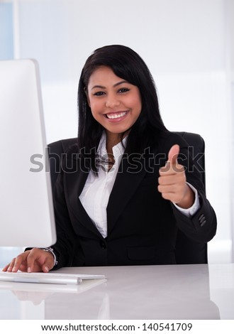 Young Businesswoman Working In Office And Showing Thumb Up Sign - stock photo