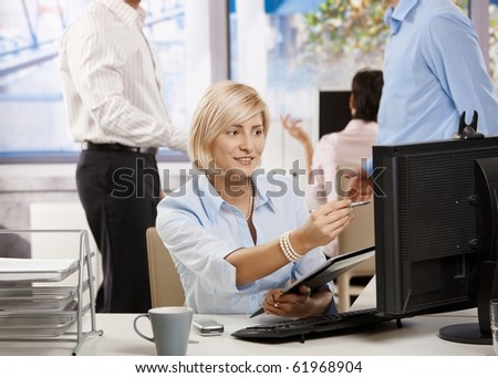 Young businesswoman working in office, checking data on screen holding notepad.?