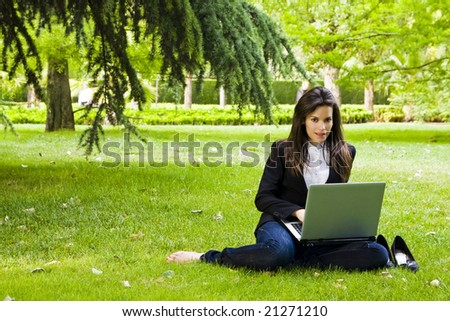 Young businesswoman working in the park.
