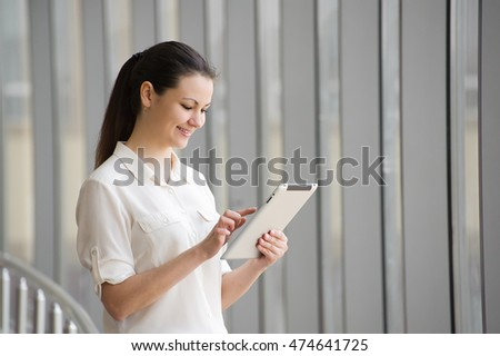 young businesswoman working on ipad while standing by window in office beautiful young female model beautiful bright office