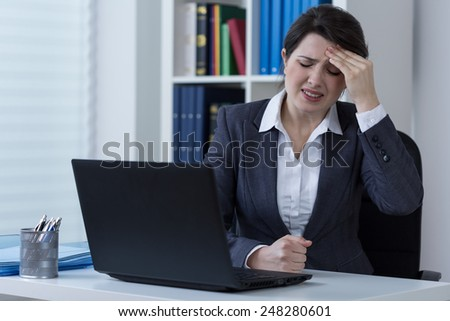 Young businesswoman working on laptop and terrible headache - stock photo