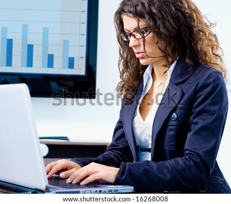 Young businesswoman working on laptop computer in meeting room at office with TV-screen and graph in background. - stock photo