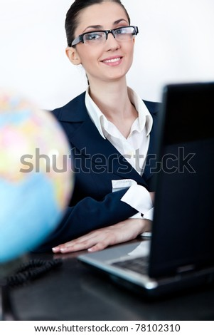 young businesswoman working on laptop in office, looking at camera - stock photo