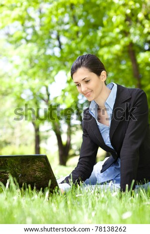 young businesswoman working on laptop in park - stock photo