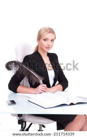 Young businesswoman working on white background and looking into camera. beautiful young woman writing at table using feather - stock photo