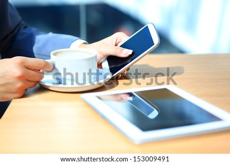Young businesswoman working with modern devices, digital tablet computer and mobile phone.