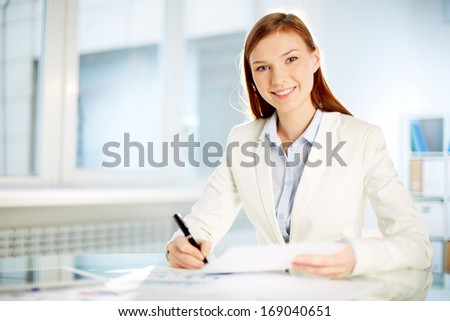 Young businesswoman working with papers in office