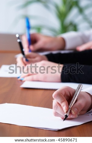 Young businesswoman writing document in office