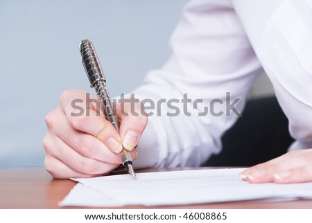 Young businesswoman writing document in office - stock photo