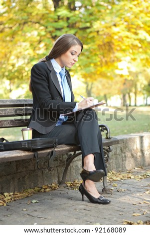 young businesswoman writing , making note on break , outdoor